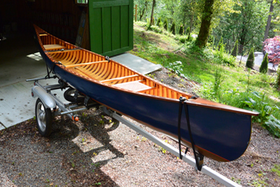 Blue wood and canvas canoe with Danuu cover